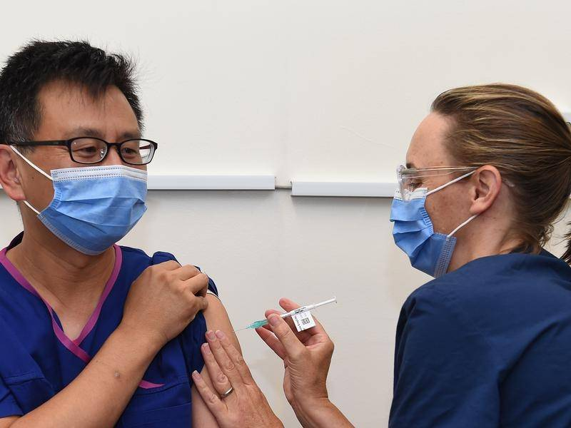 Victoria's Deputy Chief Health Officer Allen Cheng gets the Pfizer jab from nurse Karen Lasky.